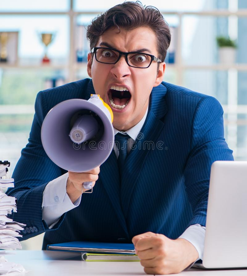 Angry aggressive businessman with bullhorn loudspeaker in office. The angry aggressive businessman with bullhorn loudspeaker in office royalty free stock images