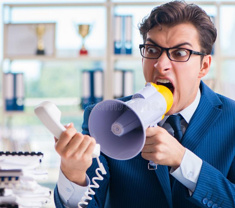 Angry aggressive businessman with bullhorn loudspeaker in office. The angry aggressive businessman with bullhorn loudspeaker in office royalty free stock image