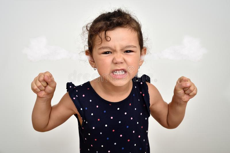 Angry and aggressive young girl with steam blowing out of her ears royalty free stock photos