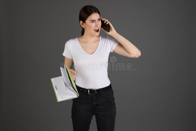 Angry agressive brunette businesswoman in white t-shirt. With notebook in hand talking on the phone with her subordinates,  over grey background royalty free stock images