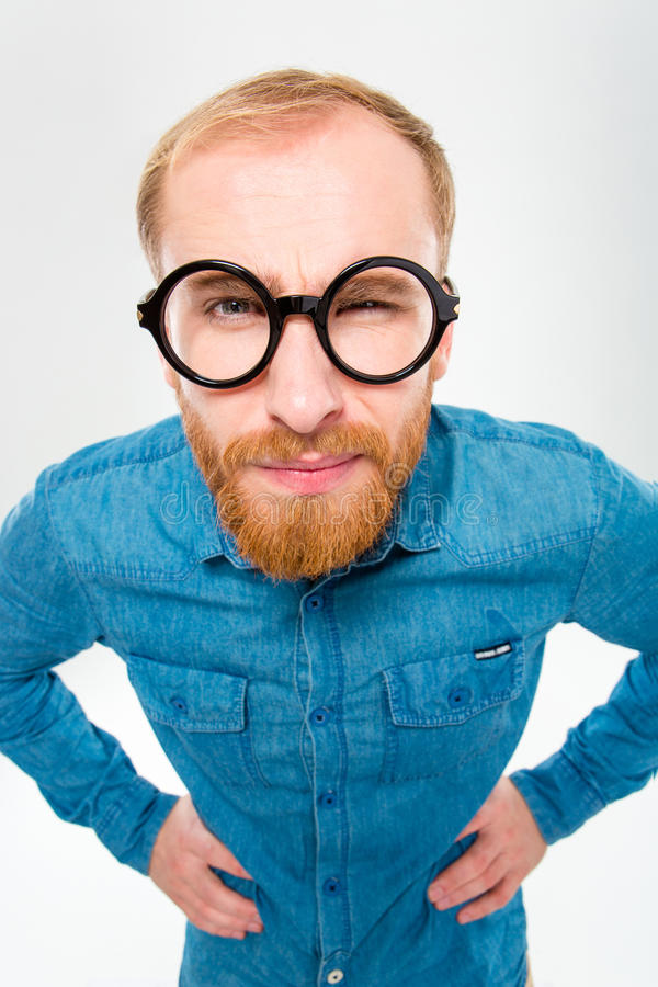 Angry amusing young man with beard in funny round glasses stock photography