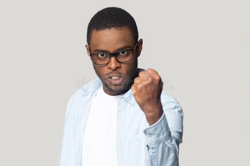 Angry annoyed african american millennial man showing clenched fist. stock photography