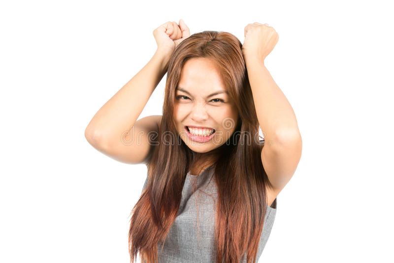 Angry Annoyed Asian Girl Slamming Fists Tantrum. An angry, annoyed Asian girl in gray with light brown hair, gritting her teeth, raises and swings her fists stock images