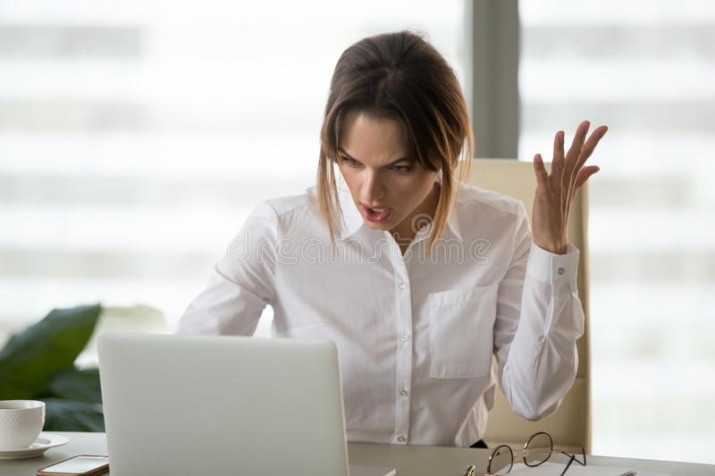 Angry annoyed businesswoman hates not working stuck laptop in of. Angry annoyed businesswoman hates not working stuck laptop, furious office employee feels mad royalty free stock photos