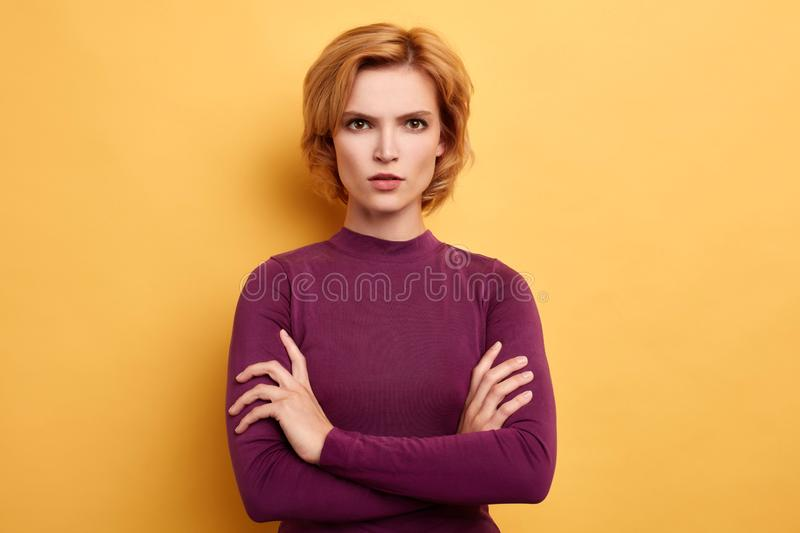 Angry annoyed youngwoman keeping arms crossed and looking at the camera. Angry annoyed youngwoman keeping arms crossed and staring at camera with sceptical and stock photos