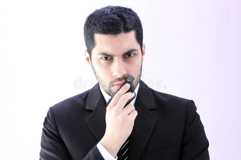 Angry arab business man with gun. Image of arab business man wearing black suit and holding pistol royalty free stock photos