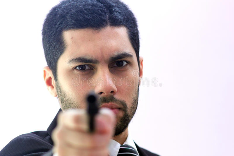 Angry arab business man with gun ready to kill. Image of arab business man wearing black suit and holding pistol and feeling despair stock photography