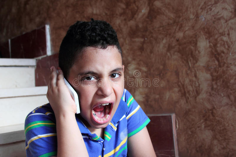 Angry arab muslim child talking in mobile phone stock photo