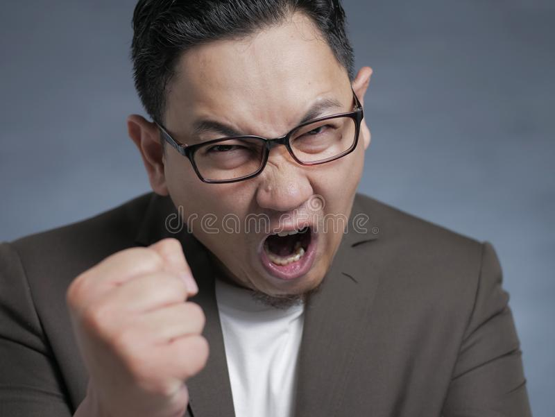 Angry Asian businessman showing his fist, ready to fight while screaming stock photos