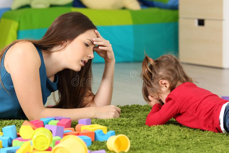 Angry baby and tired mother in a room royalty free stock photos