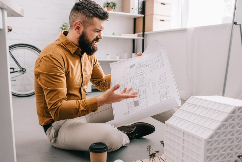Angry bearded adult male architect holding blueprint and working on project royalty free stock photo