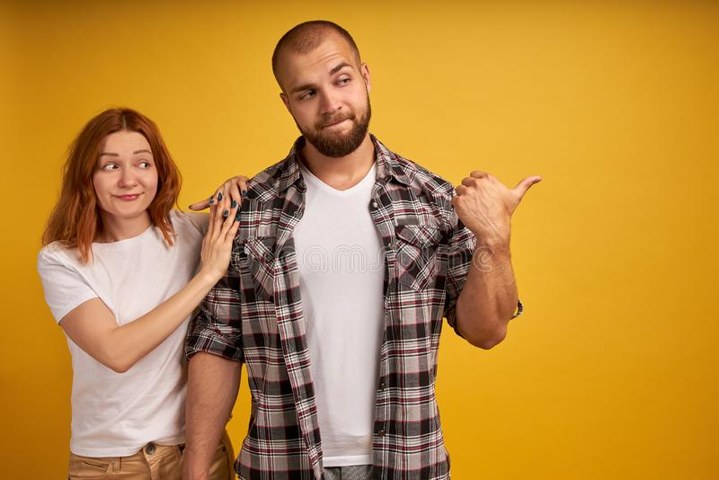 Angry bearded man looks strict and dissatisfied, points away with thumb, demonstrates something he doesnt like, woman with red stock photo