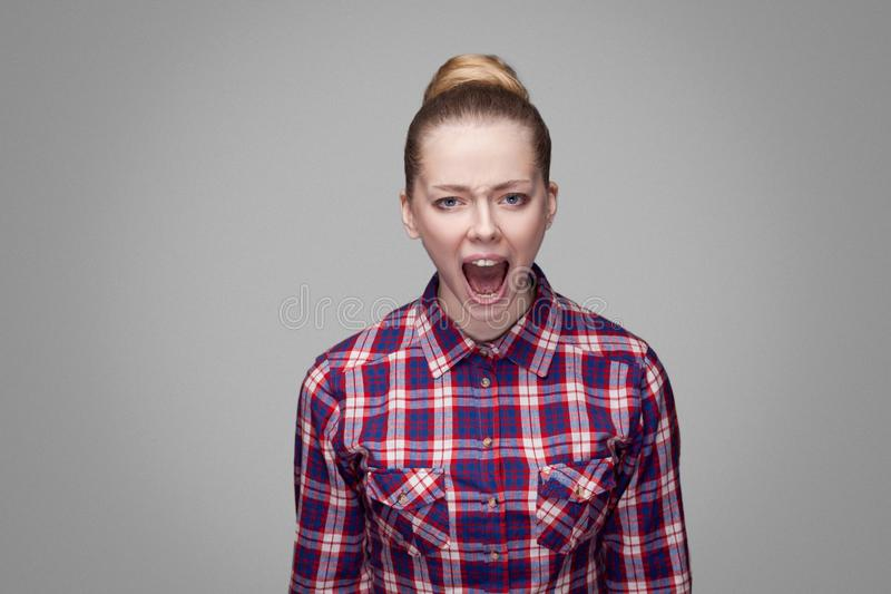 Angry beautiful blonde girl in red, pink checkered shirt, collected bun hairstyle, makeup standing and looking at camera with and. Screaming. indoor studio shot royalty free stock photography