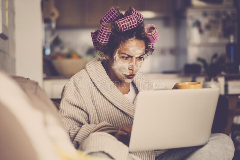 Angry and beautiful young people middle age caucasian woman with wellness cream mask on the face - looking the web for home made. Remedy - curlers for beauty royalty free stock images