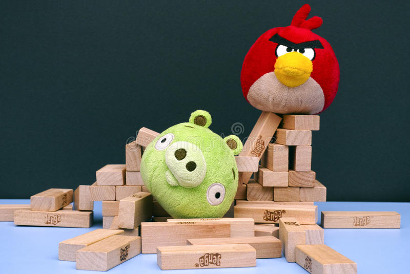 Angry Bird vs. Bad Piggies with soft toys and Jenga bricks. Tambov, Russian Federation - March 03, 2016 Angry Bird vs. Bad Piggies. Red bird broke bad pig's royalty free stock photos