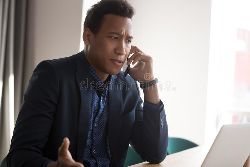 Angry black businessman disputing on phone at office royalty free stock images