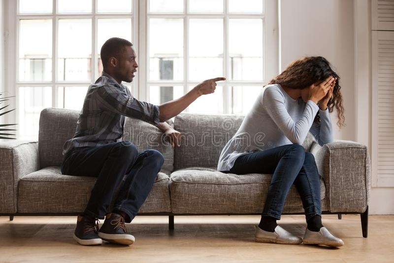 Angry black husband arguing blaming upset wife of problems. Angry black husband arguing yelling blaming upset wife of problems, jealous distrustful dominant royalty free stock photography