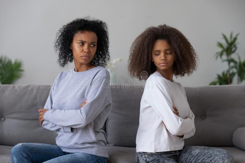 Angry black mom and daughter not talking after fight. Angry African American mother and daughter sit back to back on couch, avoid talking or looking, mad black stock photos