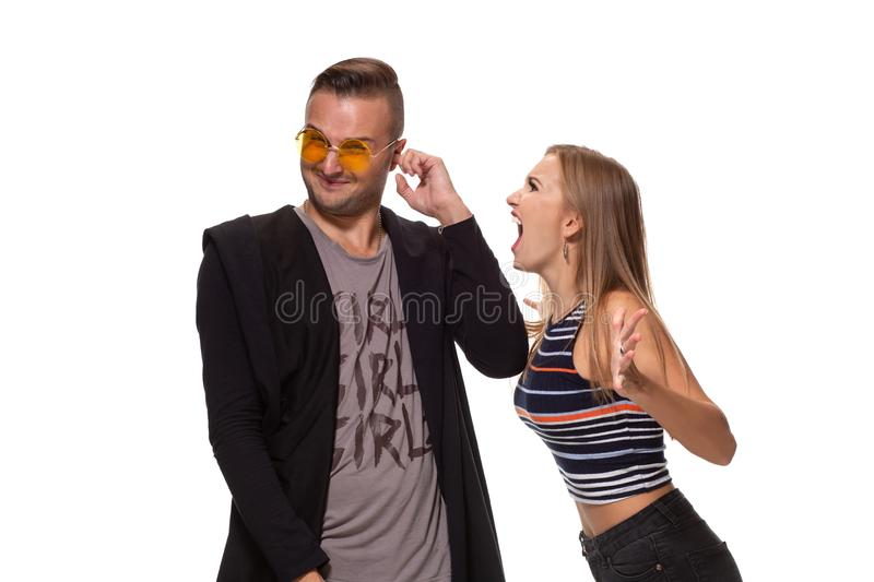 Angry blonde young European woman gestures with hands, shouts at husband who is guilty, stands together against white. Young family couple have conflict. Angry royalty free stock photography
