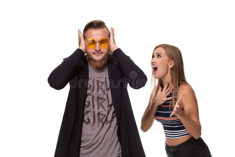 Angry blonde young European woman gestures with hands, shouts at husband who is guilty, stands together against white. Young family couple have conflict. Angry stock photos