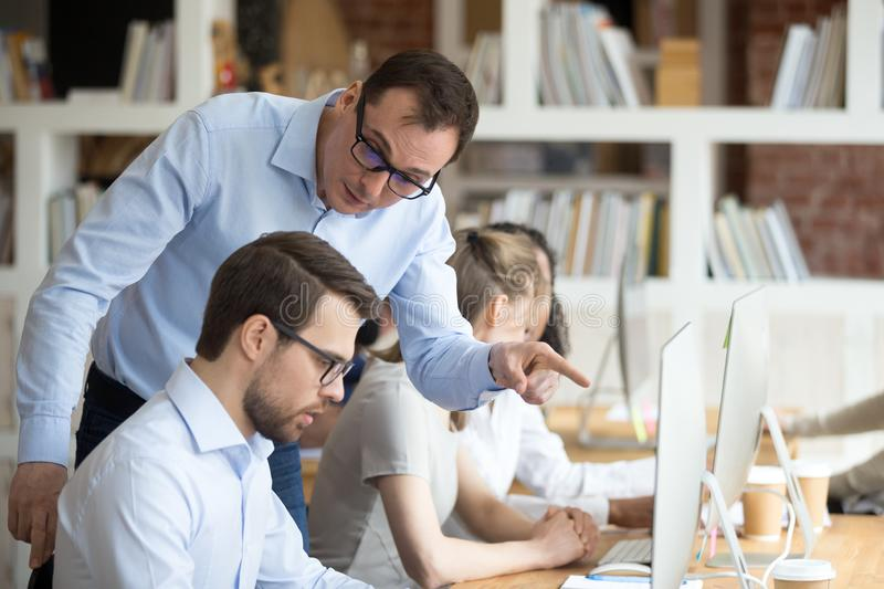 Angry boss criticizing scolding sad male employee for computer mistake. Incompetence at workplace, mad leader reprimanding rebuking shouting at subordinate lazy stock photo