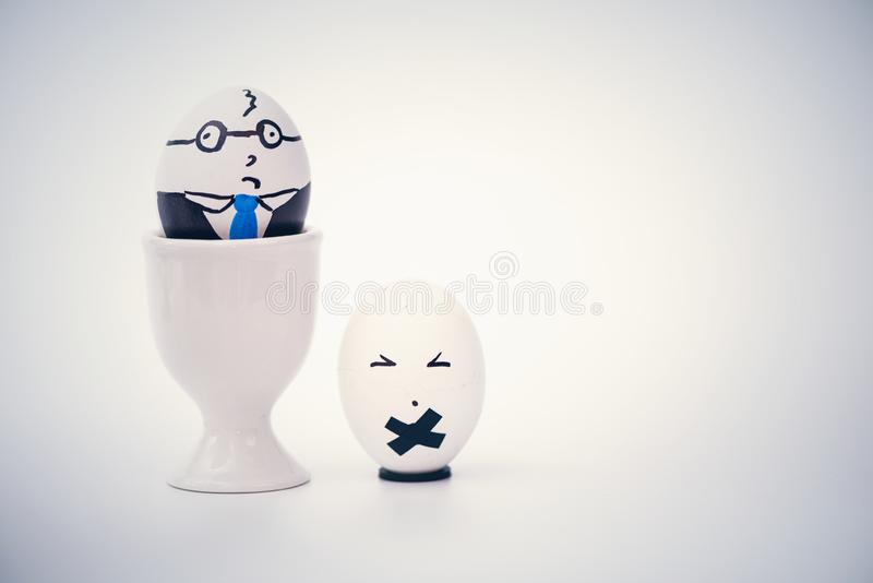 Angry boss and employee in the form of white eggs.  Creative. Concept royalty free stock photos