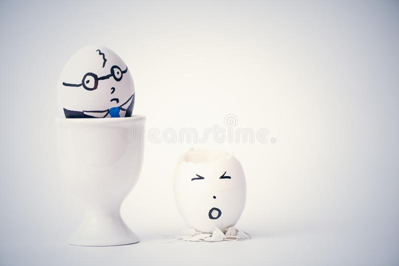 Angry boss and employee in the form of white eggs.  Creative. stock photography