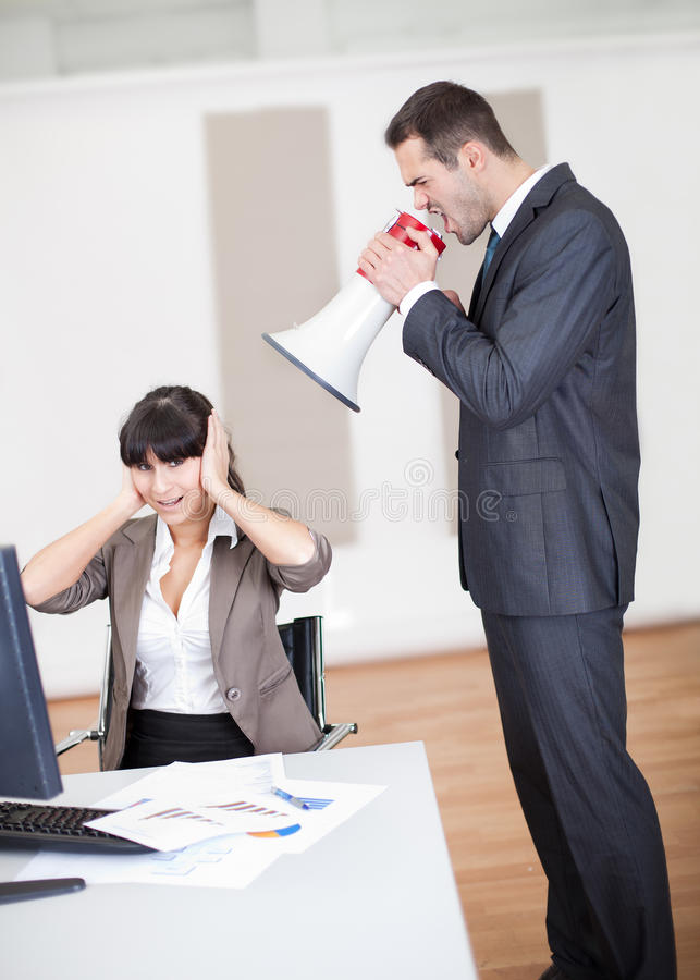 Angry boss screaming at employee. Angry businessman screaming at employee at the office in megaphone royalty free stock photography