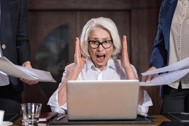 Angry boss shouting in office. Time to panic. Angry tired elderly boss shouting while working on a laptop in office and feeling tired royalty free stock photos