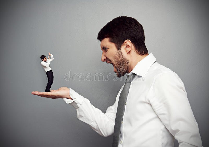 Angry boss and small scared worker royalty free stock photography