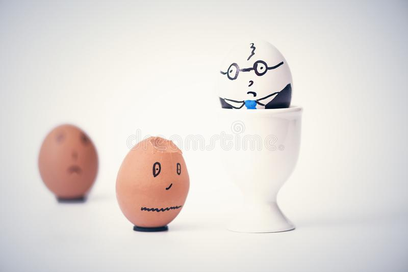 Angry boss and two employees in the form of white and dark eggs. royalty free stock photo