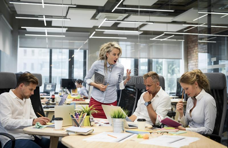 Angry boss yelling at her co-workers. In the meeting stock image