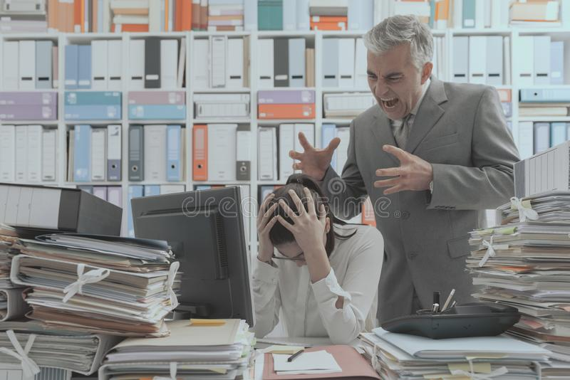Angry boss yelling at his young employee stock photography