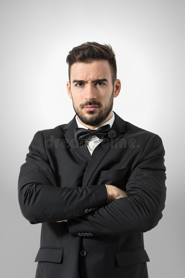 Angry bossy man in tuxedo with crossed arms intense looking at camera. Portrait over gray studio background royalty free stock photography