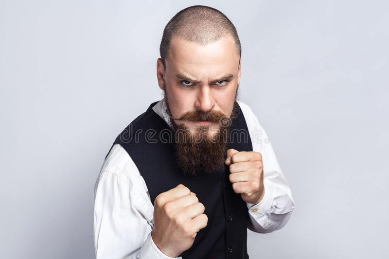 Angry boxing. Handsome businessman with beard and handlebar mustache looking at camera with angry face and fist. Studio shot, on gray background stock image