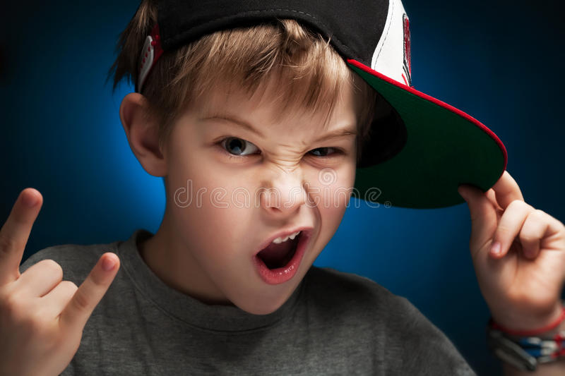 Angry boy rapper is posing a face. Boy rapper poses a face stock image