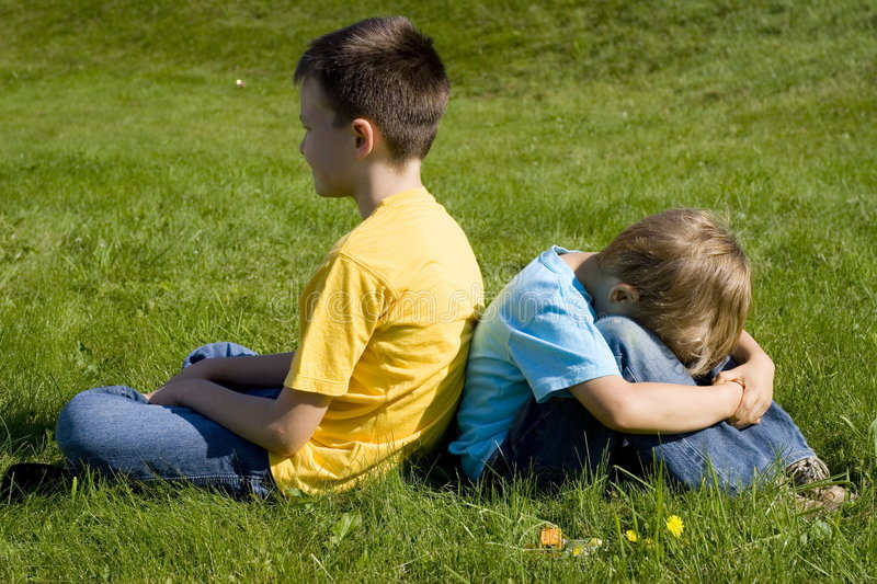 Angry Brothers. Two angry brothers sitting on grass back to back. The younger brother is leaning over and hiding his face stock photography