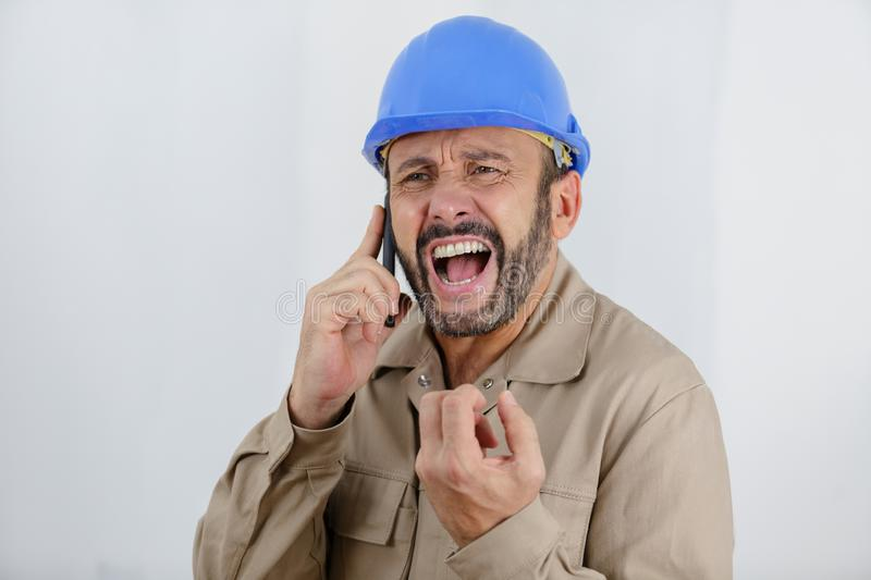 Angry builder or constructor yelling at somebody on phone. Angry royalty free stock photography