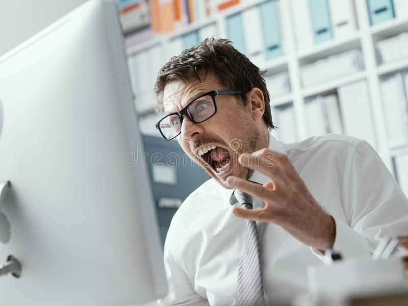 Angry business executive shouting at the computer stock image