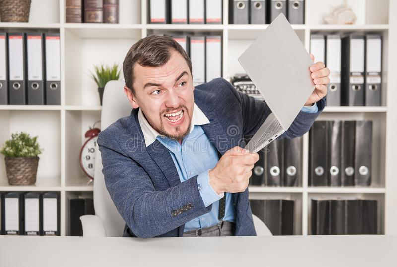 Angry business man breaking laptop. Stress concept royalty free stock photos