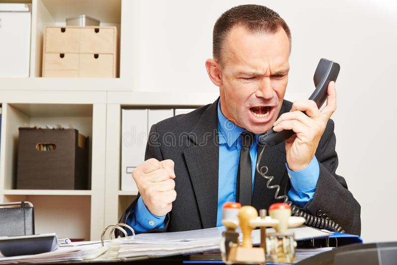 Angry business man screaming at phone stock photos