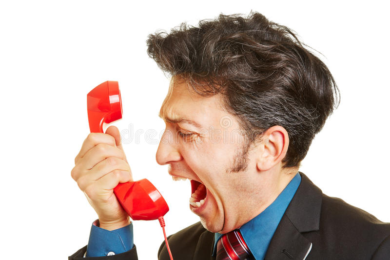 Angry business man screaming into phone receiver. Angry business man screaming loudly into a red phone receiver stock photos
