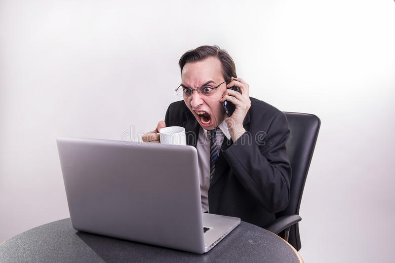 Angry business man talking on a cell phone and screaming on his laptop in the office stock photos