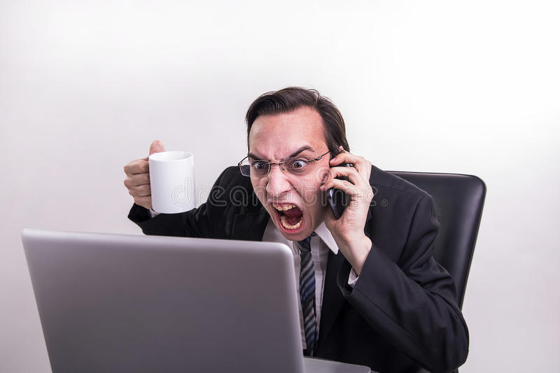 Angry business man talking on a cell phone and screaming on his laptop in the office. Angry and frustraded business man talking on a cell phone and screaming on stock images
