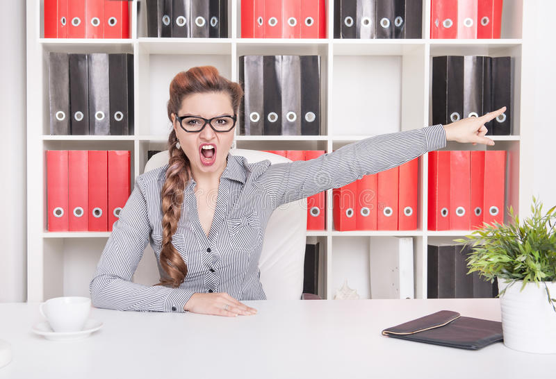 Angry business woman boss pointing out. Dismissal concept. Angry business woman boss pointing out in office. Dismissal concept royalty free stock photos