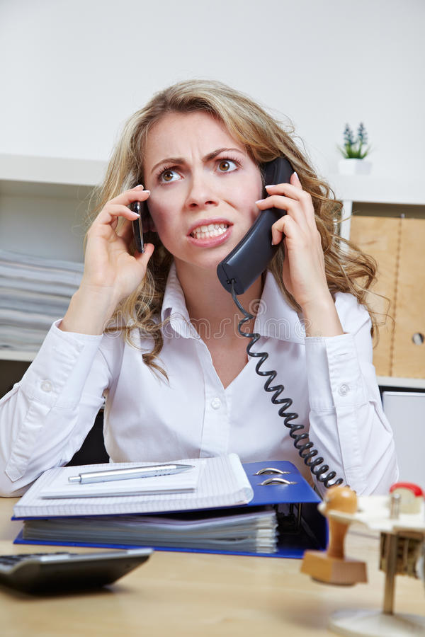 Angry business woman on the phone. Angry business woman in her office on two phones at the same time royalty free stock image