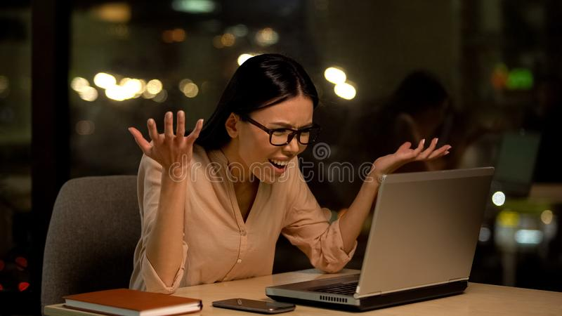 Angry business woman reading client email on laptop, work trouble, deadline. Stock photo royalty free stock photos