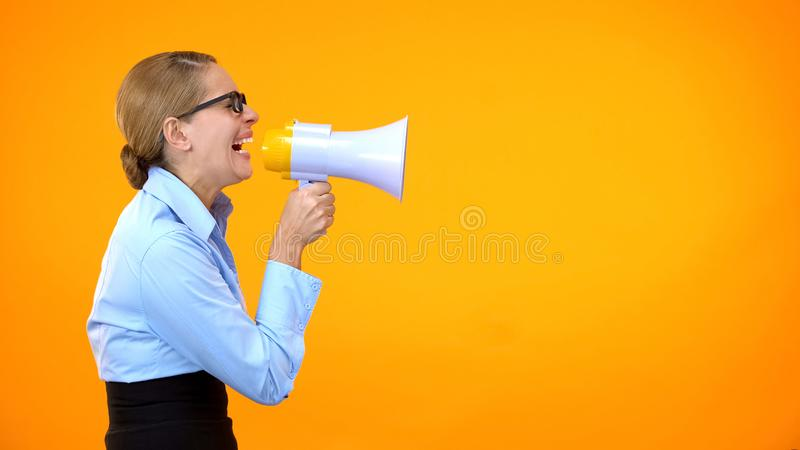 Angry business woman shouting in megaphone on orange background, leadership stock photography