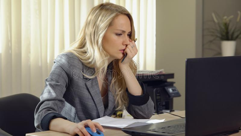 Angry business woman in suit works at the computer in office. stock photography