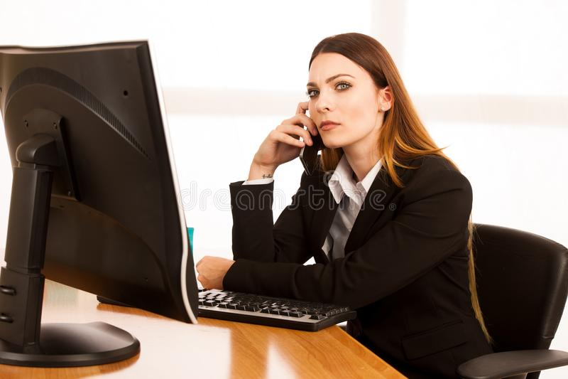 Angry business woman talks on smert phone in office at her desk royalty free stock image